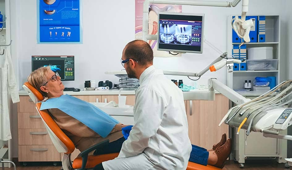 orthodontist-discusses-an-mri-scan-with-patient-dental-care-oral-health-dentist-and-old-woman