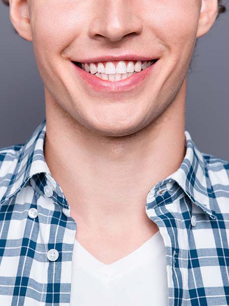 types-of-veneers-stylish-guy-blue-checkered-shirt-posing-against-grey-wall-smile-dental-care-oral-health