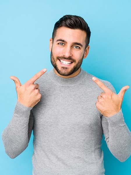 do-i-need-a-dental-crown-handsome-boy-pointing-teeth-smile-dental-care-oral-health