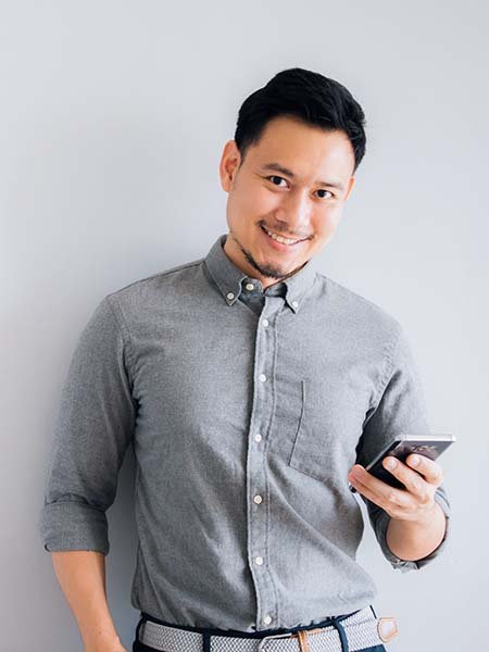 happy-smile-face-handsome-asian-man-use-smartphone-stand-isolated-gray-background-dental-care-oral-health
