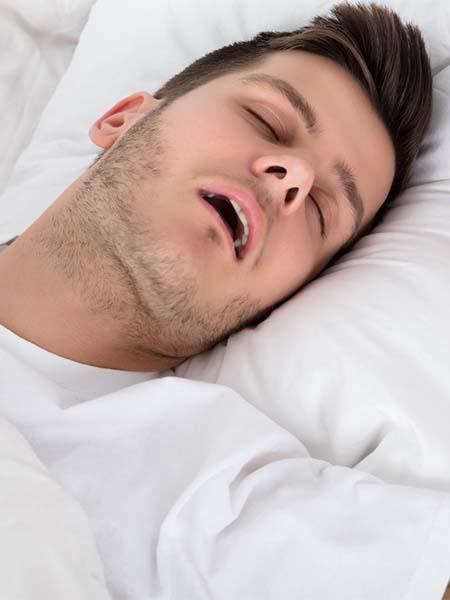what-causes-sleep-apnea-whtie-handsome-boy-sleeping-snoring