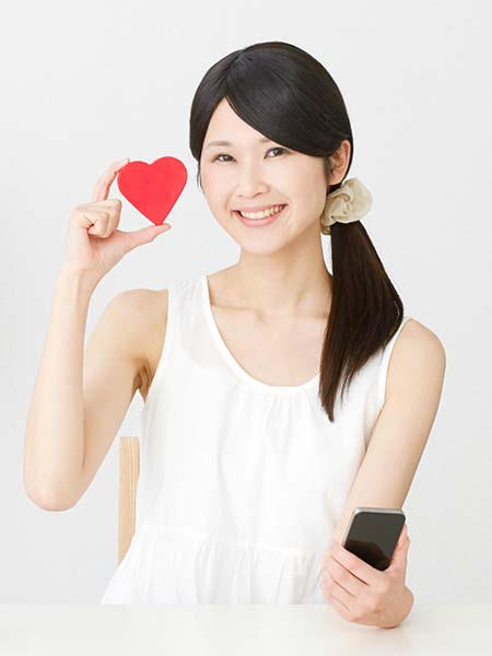 why-should-you-get-your-teeth-whitened-happy-asian-girl-smile-heart-holding-phone-dental-care-oral-health